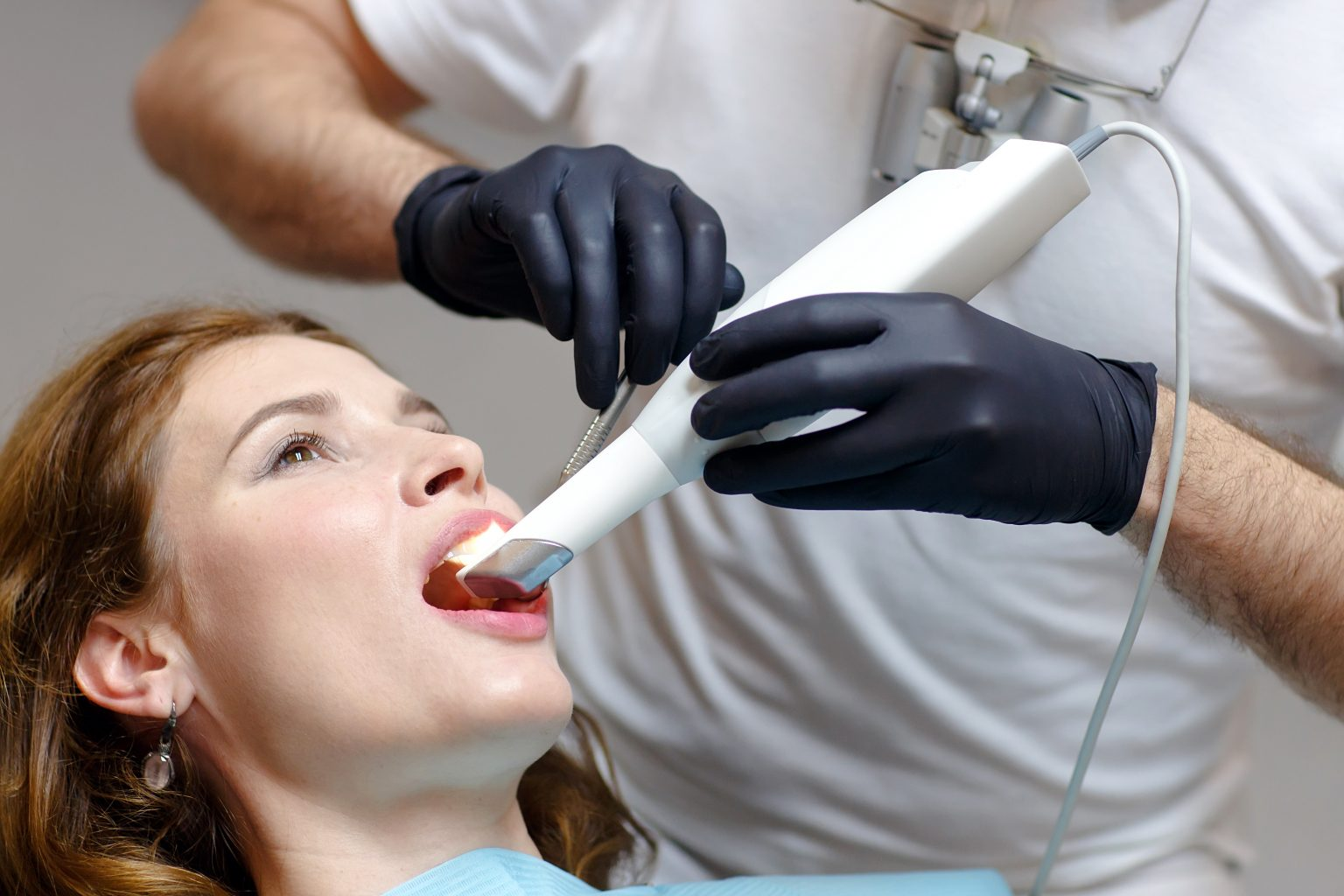 The Dentist Scans The Patient's Teeth With A 3d Scanner.