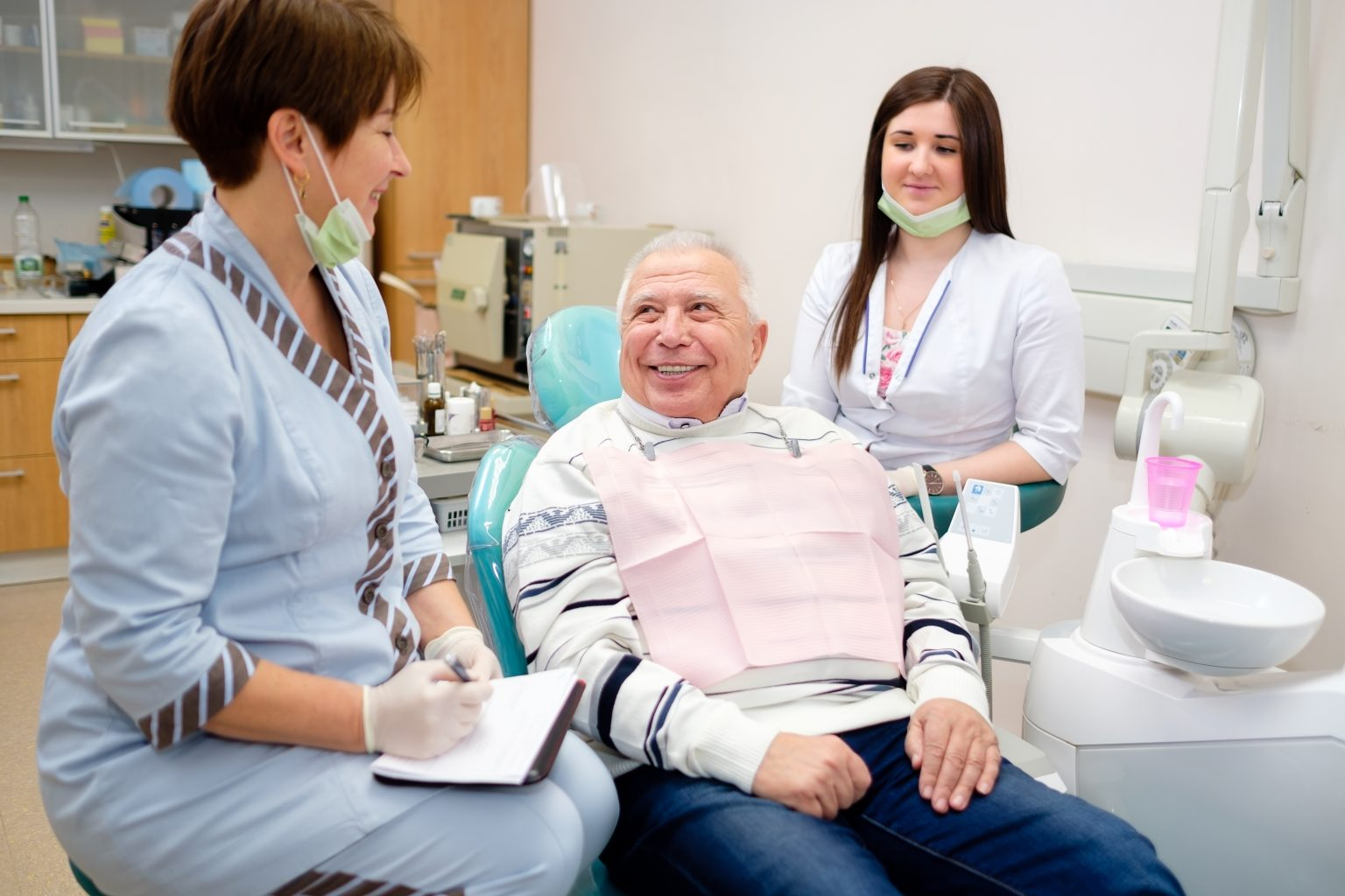 Portrait Of Senior Man, Doctor And Nurse On The First Dental Visit At Dental Office. Old Senior Patient 70 Years Old. Dentistry, Medicine And Health Care Concept.group Of People In Dental Clinic